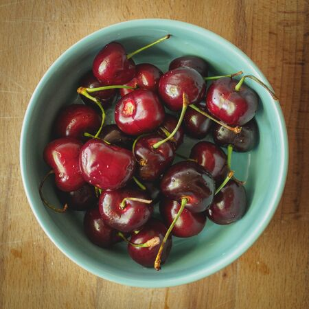 Vintage looking image of a light blue bowl full of red cherries on a wooden board. Square format. Stok Fotoğraf