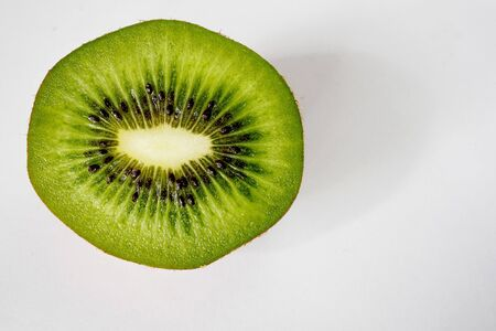 Portion of a slice of kiwi isolated on white background, top view, landscape format. Close-up.