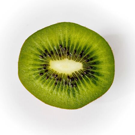 Portion of a slice of kiwi isolated on white background, top view, square format. Close-up.