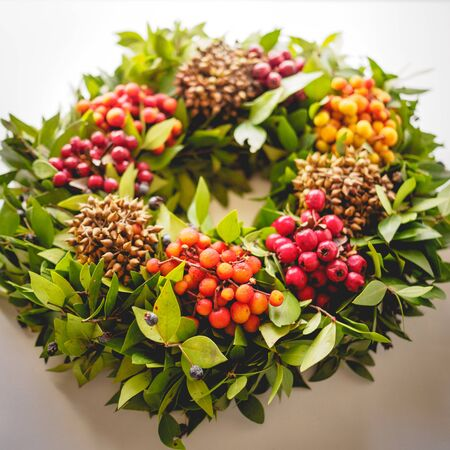 Top view of a festive Christmas wreath with red and orange berries on a white background. Vintage filter. Square format. Stok Fotoğraf