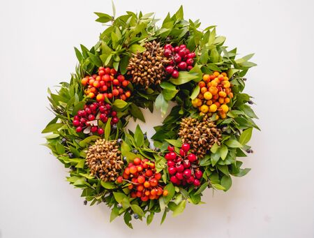 Top view of a festive Christmas wreath with red and orange berries on a white background. Vintage filter. Landscape format.
