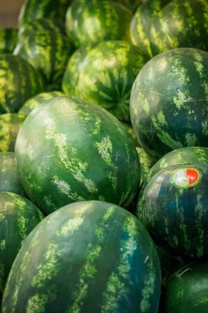 Watermelons on sale in a food market. Portrait format.