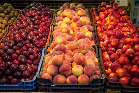 Different varieties of peaches on sale in a local market. Landscape format.