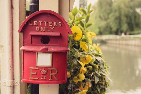 Vintage red letter box with yellow flowers and the river Cambridge in the background. Landscape format.