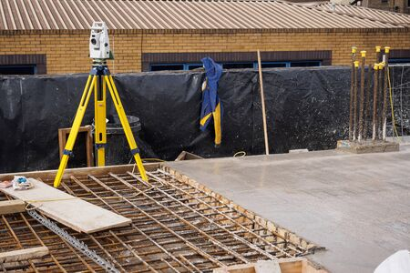A theodolite on use on a partially cast concrete slab in a construction site. Landscape format.