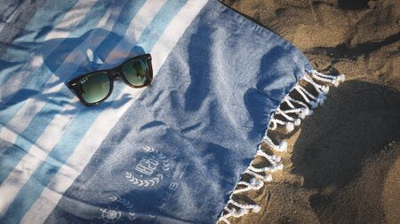 Sunglasses left on a beach towel at sunset.