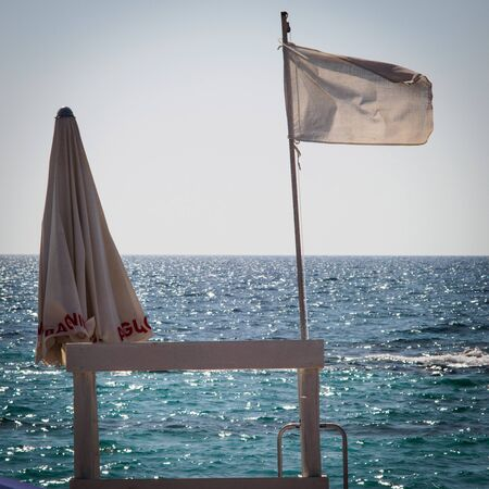 White waving flag on a lifeguard chair on the beach of Padula Bianca. Square format. Banco de Imagens - 132123473