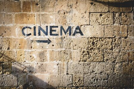 The word cinema and an arrow pointing the right side painted in black on a stone wall. Landscape format.