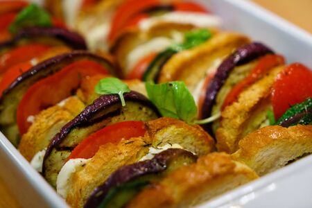 Flat lay top view of oven baked sliced vegetables (tomatoes, aubergines and courgettes) with mozzarella cheese and baguette slices dressed with basil. Stok Fotoğraf