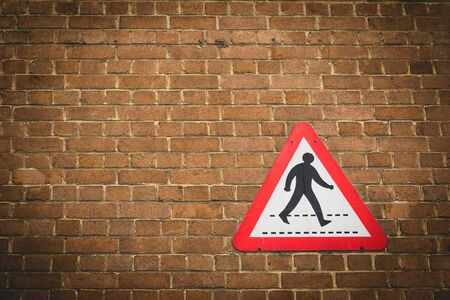 Vintage pedestrian crossing sign on a brick wall background. Landscape format.