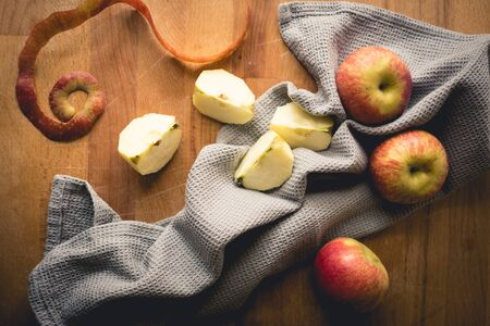 Top view of apples on a wooden chopping board with a grey kitchen cloth. Landscape format.