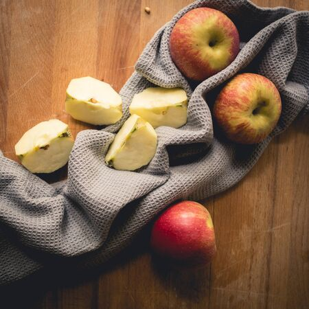Top view of apples on a wooden chopping board with a grey kitchen cloth. Square format.