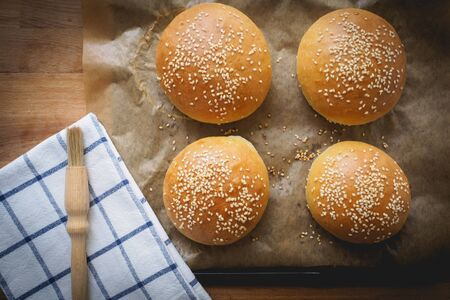 Top view of homemade sesame buns on a wooden chopping board with a striped white kitchen cloth and a pastry brush. Stok Fotoğraf