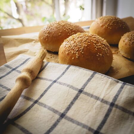 Top view of homemade sesame buns on a wooden chopping board with a striped white kitchen cloth and a pastry brush.