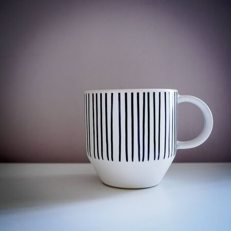 White mug with black lines decorations on a white table. Vintage look filter. Square format.
