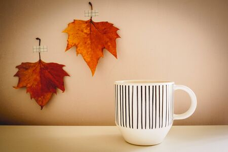 White mug with black lines decorations on a white table with two red autumn leaves on the background. Autumn concept. Vintage look filter.