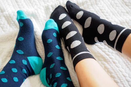 Young couple posing for a selfie feet wearing blue and white polka dotted socks. Landscape format.