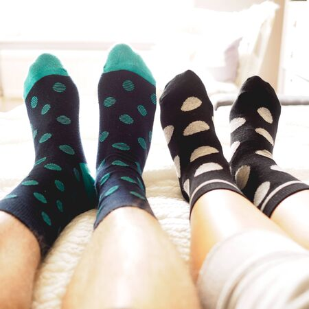 Young couple posing for a selfie feet wearing blue and white polka dotted socks. Square format. Reklamní fotografie