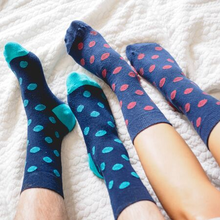 Young couple posing for a selfie feet wearing blue and white polka dotted socks. Square format.