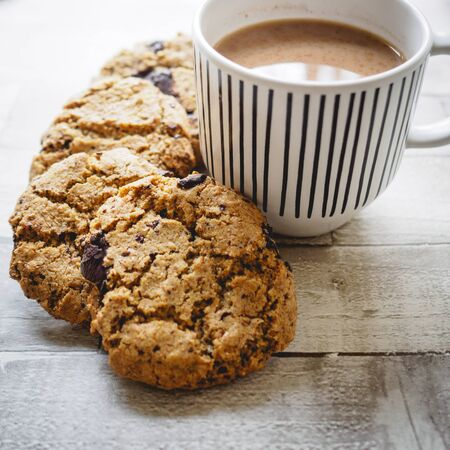 Chocolate chip cookies and a mug of tea on a white wooden table. Flat lay. Square format. Stok Fotoğraf
