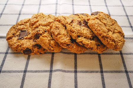 Chocolate chip cookies on a white and blue tea towel. Flat lay. Landscape format.