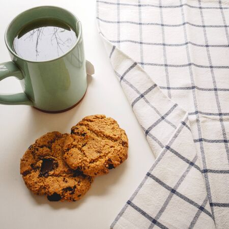 Chocolate chip cookies and a green mug of tea with a tea towel on a white table. Flat lay. Square format