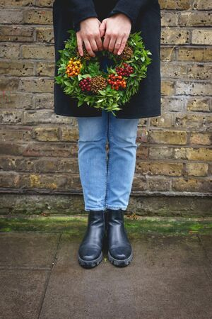 Young girl holding a Christmas fruit wreath near Columbia Road Flower Market in East London. Stok Fotoğraf