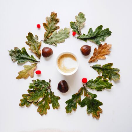 Top view of a cappuccino white mug surrounded by green and yellow leaves, chestnuts and red pompons. Square format.