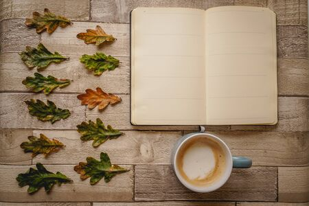Top view of an open notebook and a cappuccino mug with green and orange leaves on a wooden board. Landscape format.