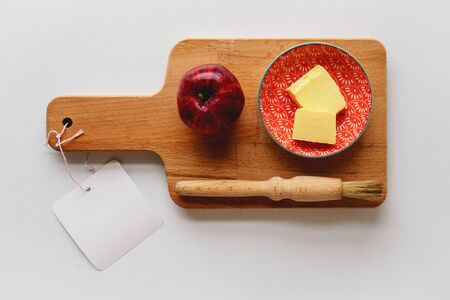 A red apple, a small plate with butter and a baking brush on a wooden chopping board with a white tag. Ingredients for an apple pie. Food concept.
