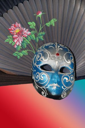Theatrical mask against a fan lying on a table photo