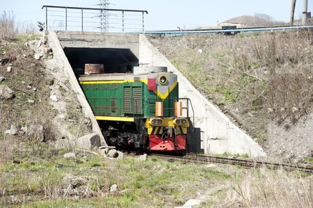Diesel locomotive with vagons leaving a tunnel photo