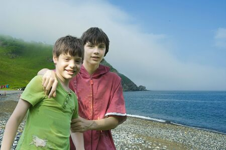 Two white boys on seacoast have a rest and play photo