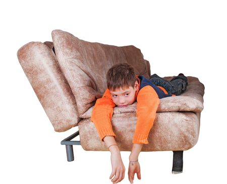 The boy lies on a sofa and smiles is isolated Stock Photo - 8062295