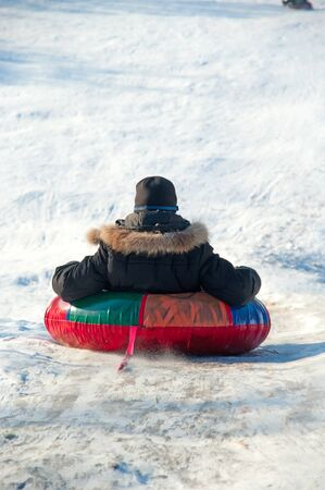 sledging people: winter fun. one kid in red sledging downhill. Stock Photo