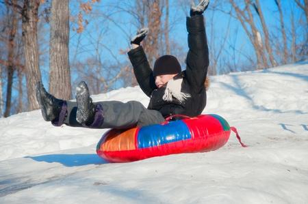 sledging: divertimento invernale. un bambino in slittino rosso in discesa.