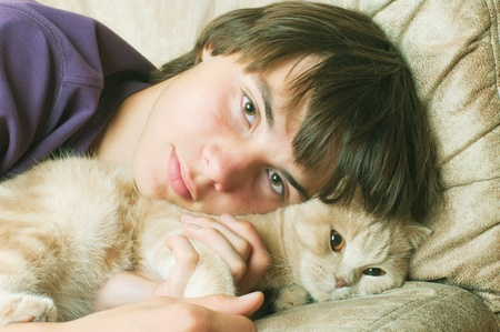 Portrait of young man with long hair with kat photo