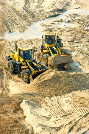 Bulldozer and a lorry load sand on district