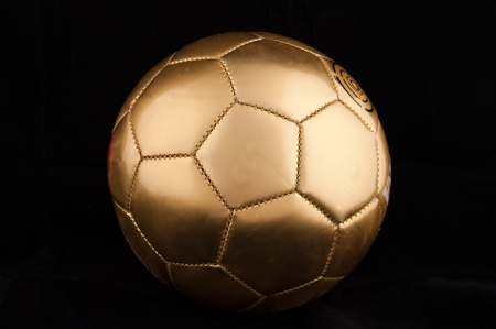 Gold soccer ball on  the black background photo