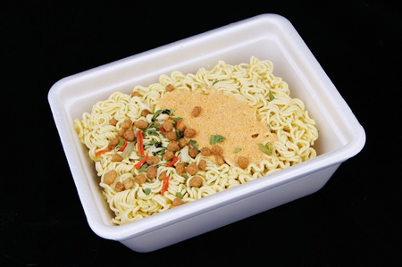 A block of Instant noodles in  disposable tablewareon black background photo