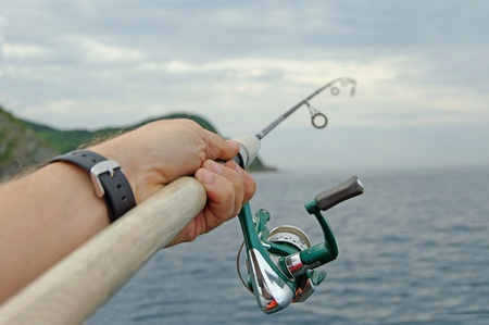 spinning reel: spinning and sea  on the fishing at summer