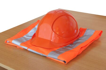 yellow high visibility vest and protective helmet on the table photo