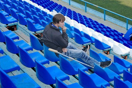 Injury player sits in an empty stadium with a medical crutch Stock Photo