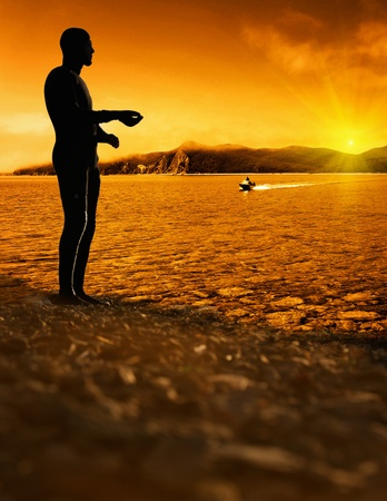 man  standing on wet sand at bright sunset background photo