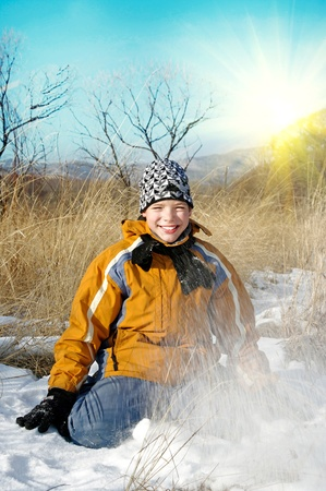 armful: portrait of a teenager in winter clothes on blue sky backgroundthrows an armful of snow