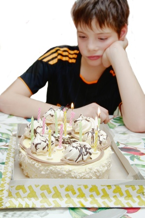 birthday - a sad holiday, the teenager sitting on the background of cake with candles sad, focus on the cake