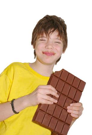 niño sin camisa: el chico de la camisa amarilla está comiendo una barra de chocolate grande Foto de archivo