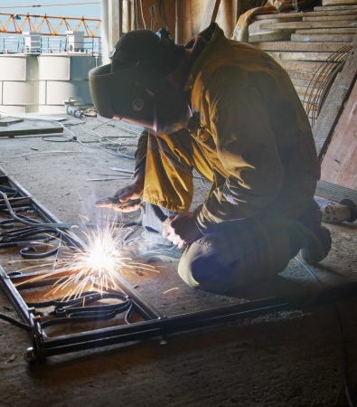 Welder with protective mask welding metal and sparks photo