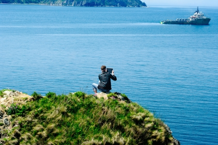 young man sitting on a rock and photographing the marine tug on the Tablet PC photo