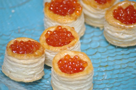 Tartlets with red caviar on blue background photo